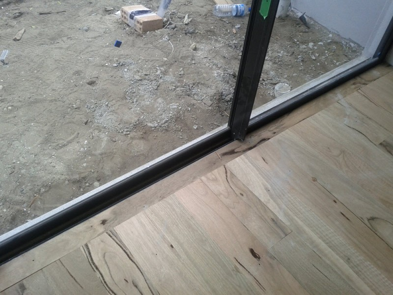 Marri floorboards - raw and unsealed, showing the finish along a sliding door