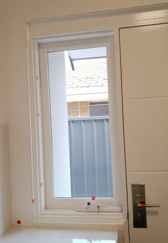 Laundry window with red dots from PCI practical completion